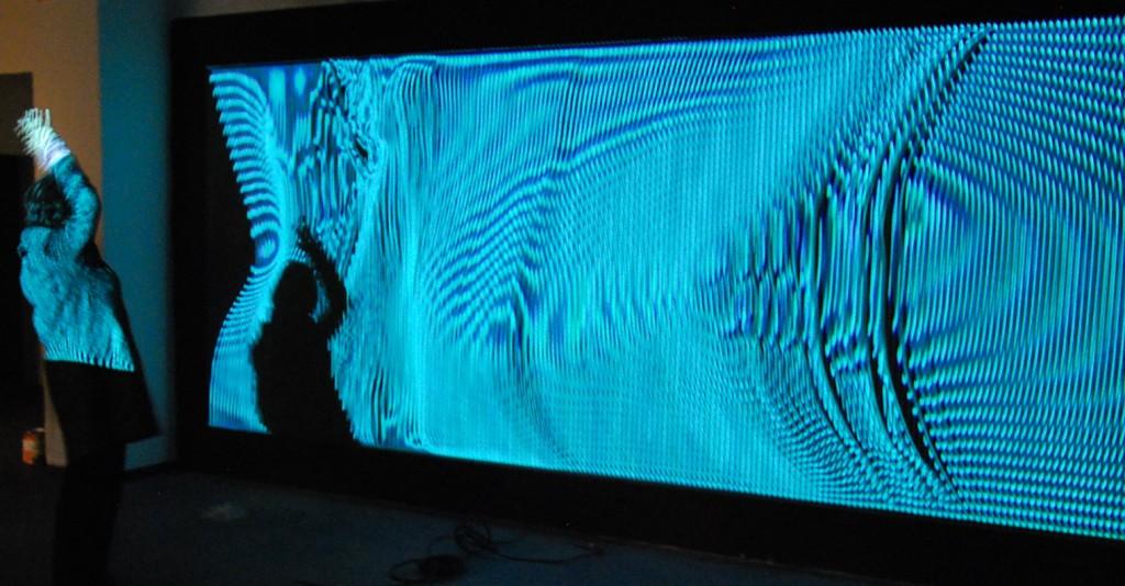 """Für das """"Fiktive Feld"""" hatten Cuppetelli & Mendoza den Ausschnitt einer schwarzen Wandfläche mit elastischen Bändern bespannt und durch eine Projektion beleuchtet, dabei simuliert das projizierte Bild die analoge Struktur des Projektionsgrundes. Foto: Wolfgang Teipel"""